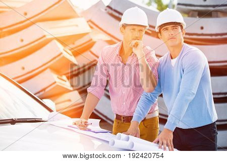 Architects with blueprints on car inspecting site