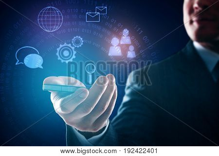 Close up of businessman's hand holding smartphone with digital business icons. Dark blue background. Communication concept