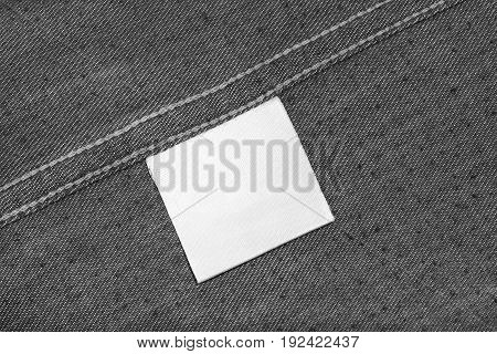 White blank clothes label on gray cloth as a background