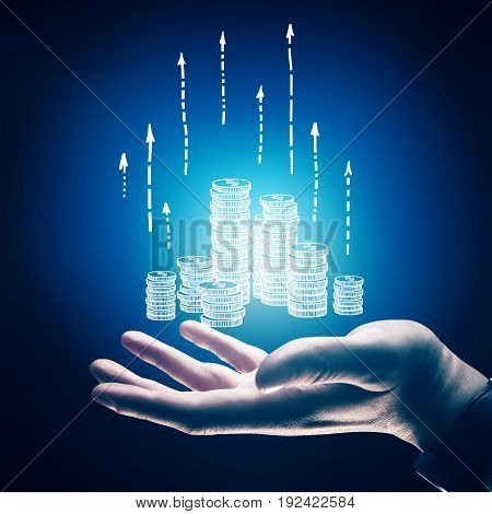 Side view of businessman's hand holding drawn coins with upward arrows on blue background. Sales concept