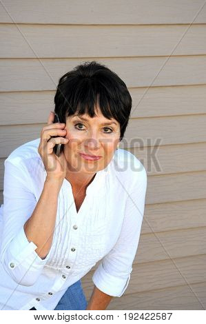 Mature female beauty talking on her smartphone outside.