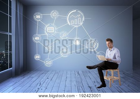 Young businessman sitting on chair and using laptop with digital business icon diagram in interior with night city view. Tech concept. 3D Rendering