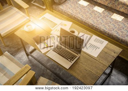 set of sofa with laptop paper chart coffee and coworking place in modern officebusiness concept.