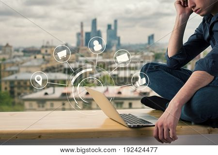 Side view of thoughtful young man sitting on wooden windowsill and looking at laptop with digital diagram. Communication concept. Blurry city background