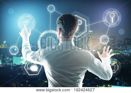 Back view of young businessman managing business icons on night city background. Touchscreen concept