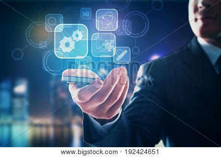 Close up of businessman's hand holding smartphone with digital business icons. Blurry city background. Technology concept
