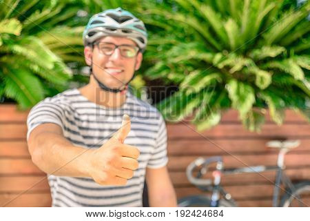 Hipster guy is making thumb up after a ride bicycle around city town. Optimistic man show his attitude to make sport and use alternative transport. Active person enjoying everyday life moments.