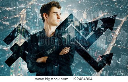 Handsome young businessman with arrows on night city background. Financial growth concept. Double exposure