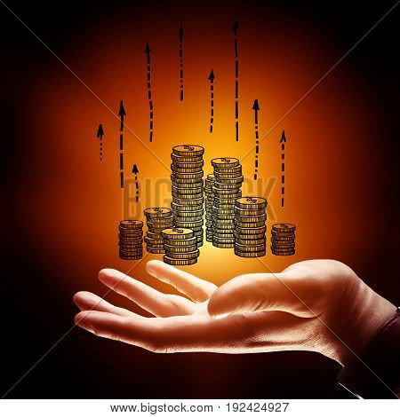 Side view of businessman's hand holding drawn coins with upward arrows on orange background. Finance concept