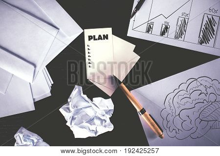 Top view of messy wooden desktop with envelopes crumpled paper sheets and sketches