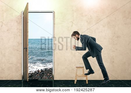 Open door with beach view and rushing businessman in concrete interior. Success concept