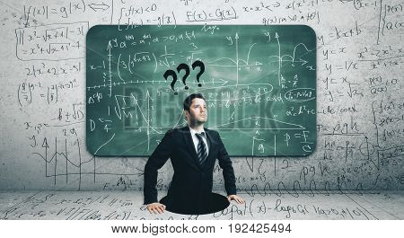 Businessman with questions standing in abstract hole. Concrete wall with mathematical formulas on chalkboard in the background. Education concept