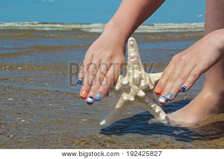 Children's sea colored manicure with a design on the nails and a starfish in hand girls summer at sea.