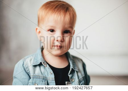 Little red-haired boy in a black T-shirt and denim jacket on white background. Toddler stylish guy.