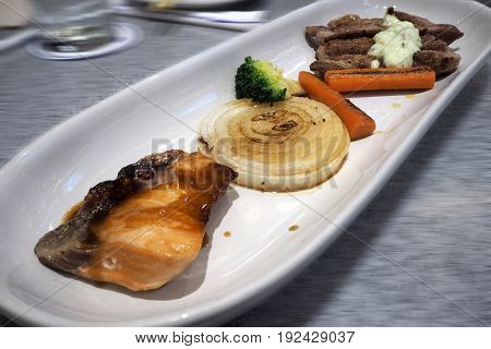 combine steak beef with fish serve on white plate