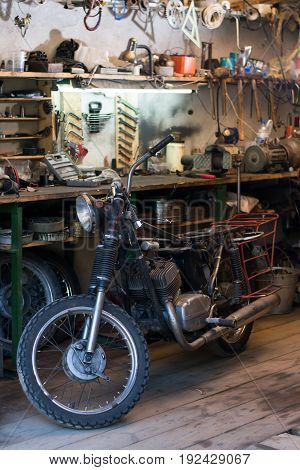 Old motorcycle which needs to be repaired in the workshop