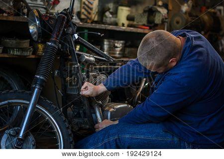 Man with tools repairing motorcycle in workshop