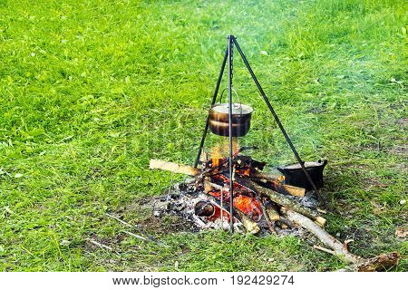 Bowler On A Tripod Over A Fire, Cooking Food In A Field Tent Camp