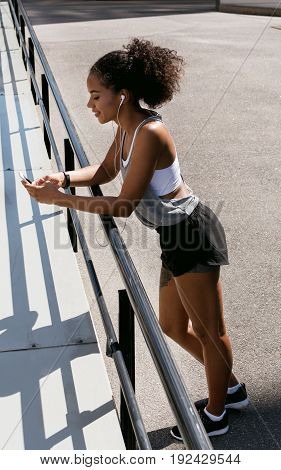 Sporty woman standing by railing, using mobile phone