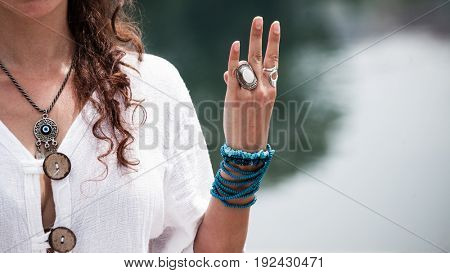 woman hand in yoga symbolic gesture mudra wearing lot of bracelets and rings outdoor closeup by the lake summer day