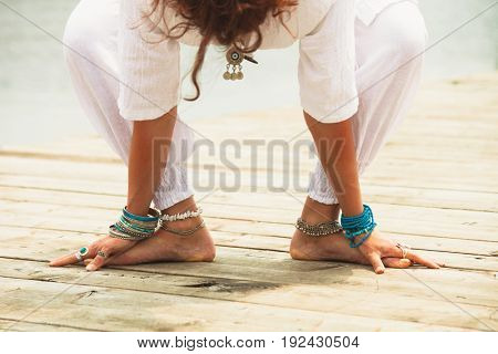 closeup of barefoot woman practice yoga outdoor by lake wearing white clothes and lot of anklets and toe ring lower body