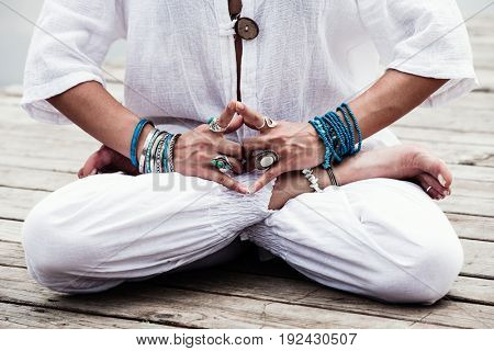 woman hand in yoga symbolic gesture mudra wearing lot of bracelets and rings outdoor closeup summer day