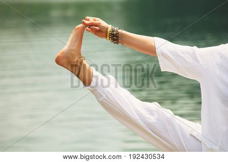 closeup of woman hand and leg practice yoga outdoor by the lake sunny summer day