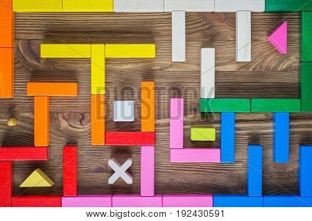 The man in the maze. The concept of a business strategy analytics search for solutions the search output. Labyrinth of colorful wooden blocks.
