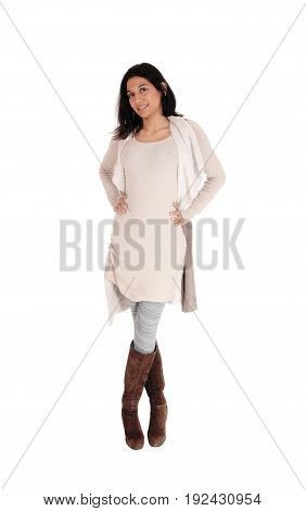 A young Hispanic woman standing from the front in a knitted dress and brown boots isolated for white background.