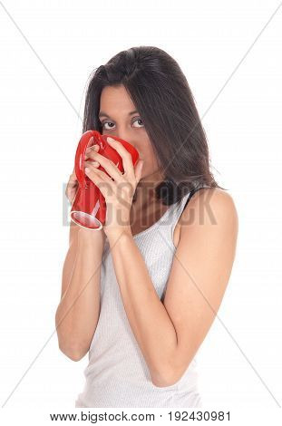A young Hispanic woman in a white t-shirt holding a red coffee mug on her mouth isolated for white background.