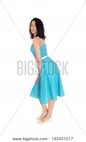 A serious gorgeous young woman standing in full length in a blue dress in profile isolated for white background.