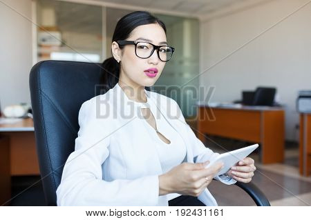 Asian young woman with tablet at office