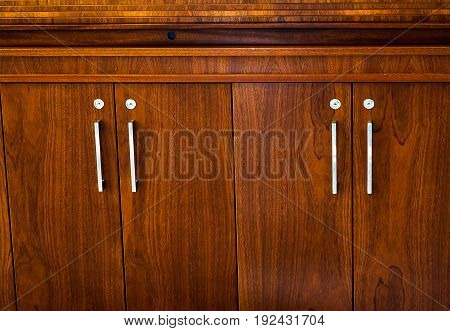 a wooden wardrobe drawer front, metal handle.