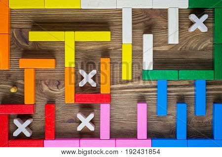 Man in the labyrinth the search for the exit top view. The concept of a business strategy analytics search for solutions the search output. Maze of colorful wooden blocks flat lay.