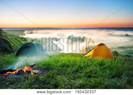 Tent camping on a hill over a misty river. Early morning. The concept of a new day and freedom.