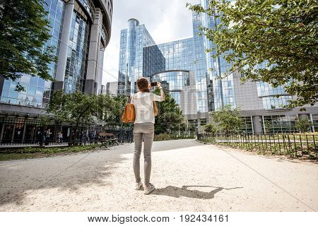 Young woman walking near the parliament building of european union in Brussel city