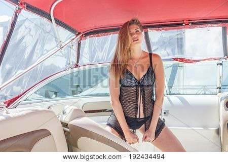 Beautiful blond woman in swimsuit, underwear posing at the port near the yacht, on the yacht