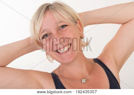 close up portrait of a attractive blond haired mid aged european woman wearing  blue top showing happy face - half body - studio shot on white background.