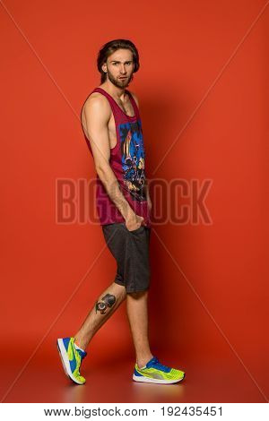 Studio portrait of handsome muscular young man on red background