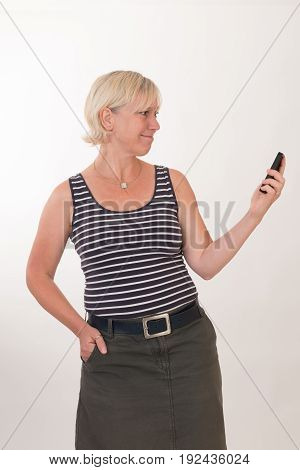 portrait of a attractive blond haired mid aged european woman wearing blue striped top acting with cellular phone - studio shot on white background.