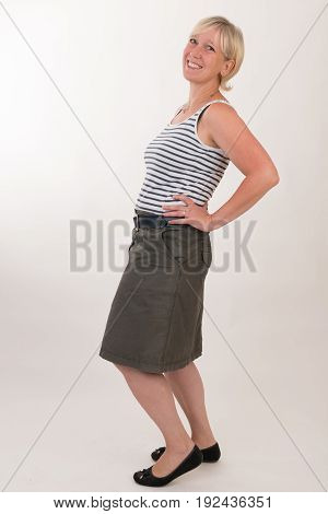 portrait of a attractive blond haired mid aged european woman wearing green skirt and blue white striped topshowing happy face - full body - studio shot on white background.