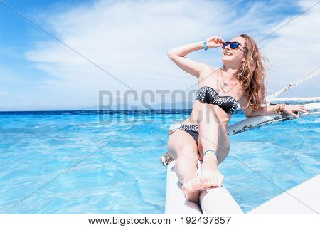 Young Caucasian Woman With Sunglasses Is Sitting On The Boat In Tropical Turquoise Sea And Getting T