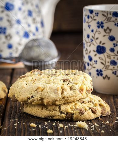 Sweet biscuits on natural wooden table with tea cup and tea strainer..