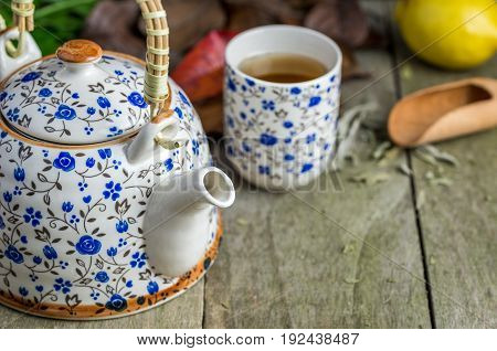 Glass of tea with tea pot and lemon on natural wooden table.