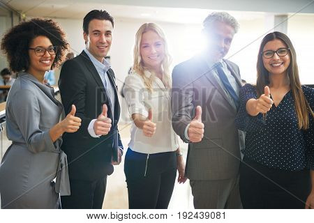Portrait of a diverse group of confident business colleagues standing together in a hallway of an office giving their approval with the thumbs up gesture