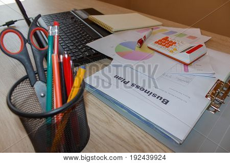 Office workplace with pen notebook calculator and computer laptop on wooden table. Business graph information diagram on wooden desk as concept