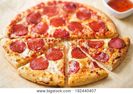Pepperoni pizza with chilli dip on parchment paper