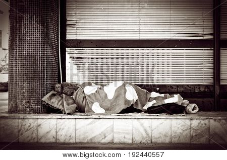 Homeless. Homeless barefooted woman sleep on the street. Social documentary street.