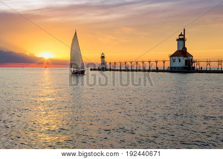 A sailboat rounds the breakwater near sunset on the longest day of the year by the Lighthouses at St. Joseph Michigan with people fishing from and walking on the pier.