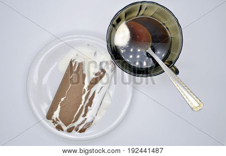 one ice-cream Lakomka ice-cream in melted chocolate on a white plate and coffee Cup with spoon with napkin isolated on white background